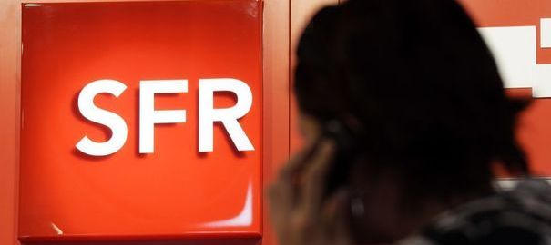 90062_a-customer-uses-a-mobile-phone-as-he-stands-next-to-a-logo-of-french-mobile-phone-operator-sfr-in-a-shop-in-nice