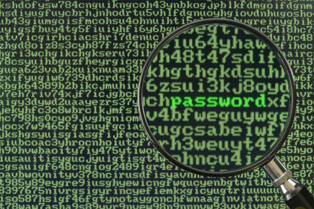 Screen full of alphanumerics depicting encryption and the word password emphasized by a magnifying glass