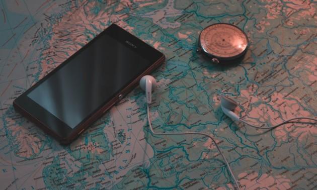 Un smartphone posé sur une carte, à côté d'une boussole