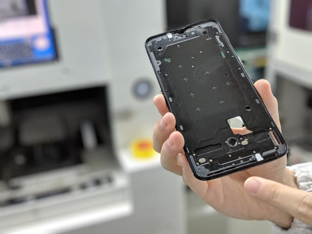 Une fois le module de caméra raccordé, la carte mère est apposée sur le smartphone, puis l'appareil photo avant est monté en haut.