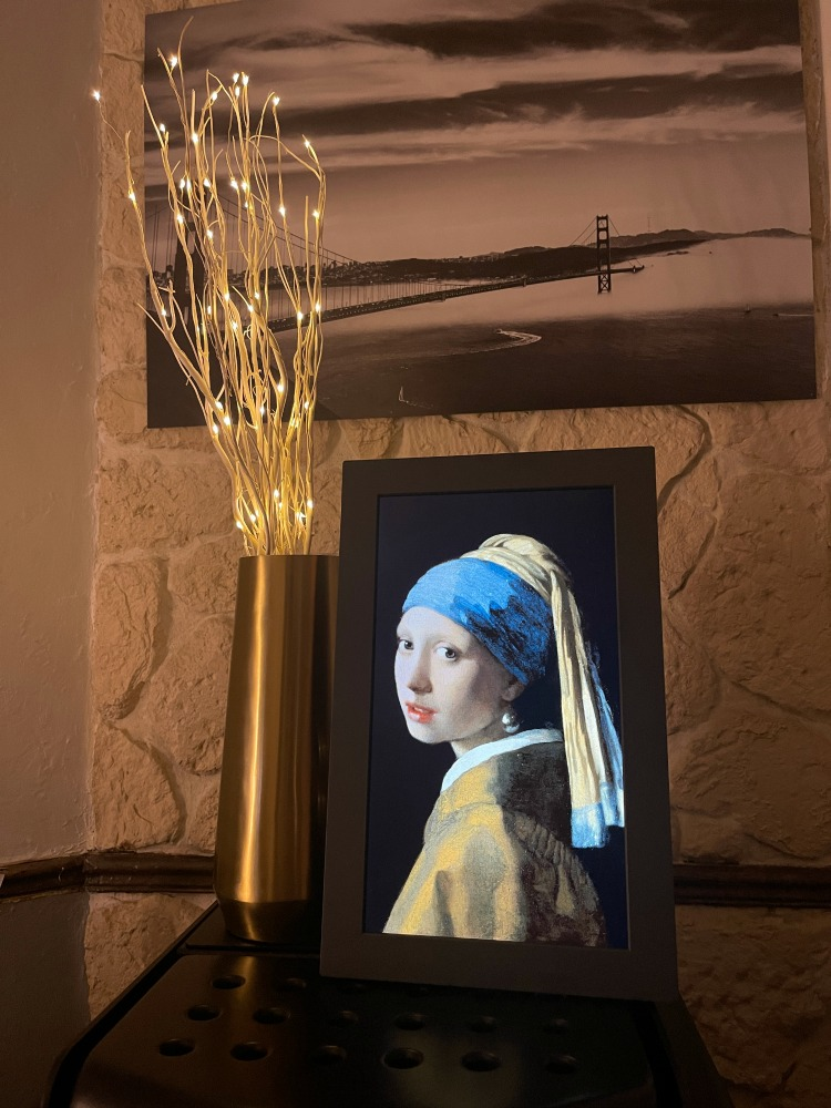 The Meural frame displaying a reproduction of Vermeer's