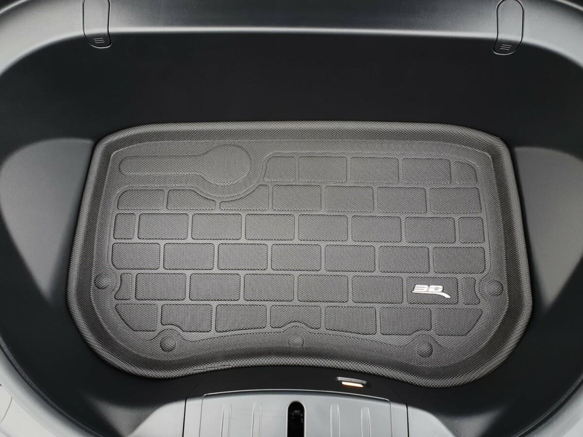 Un tapis pour le coffre avant de la Tesla Model 3, avec les crochets pour fixer des sacs