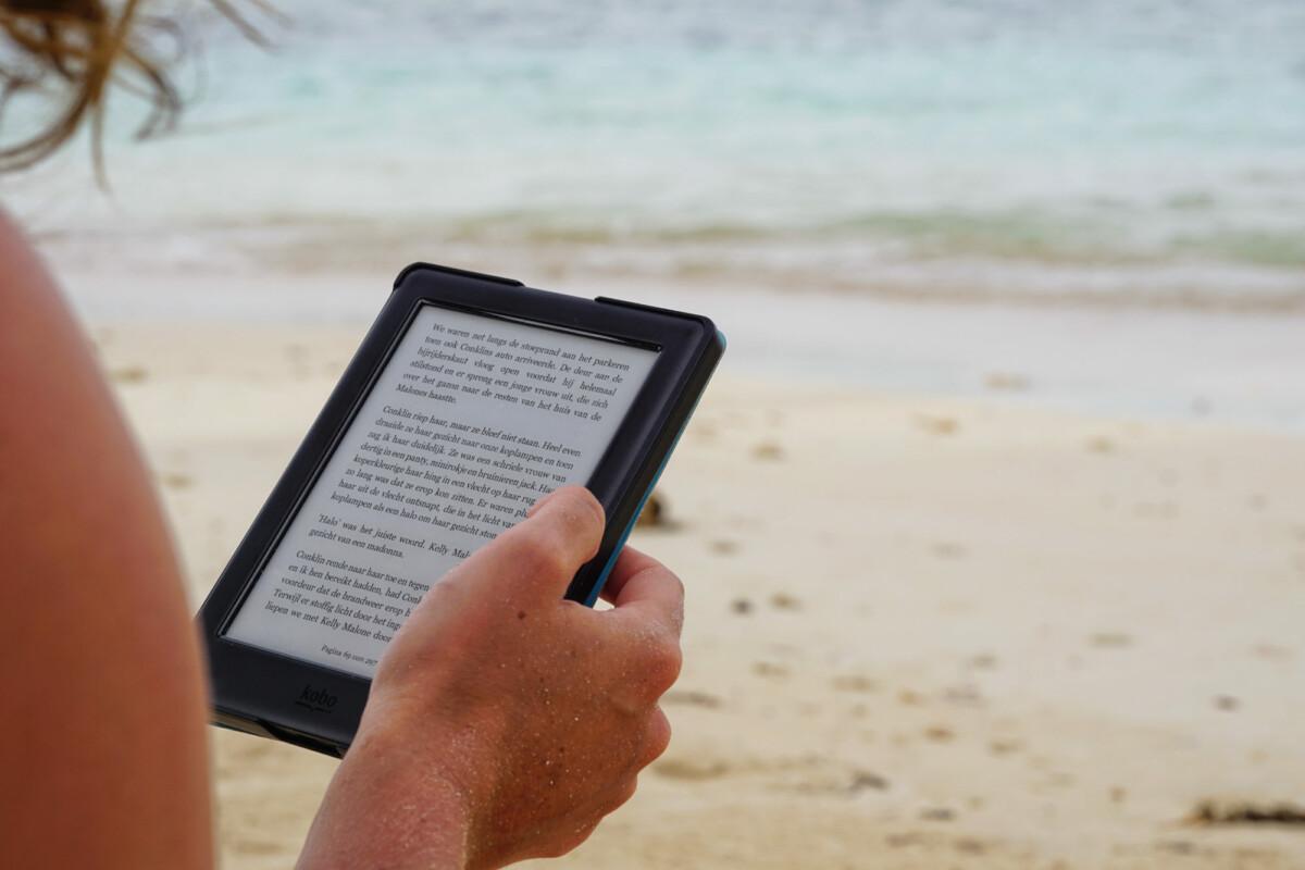 Personne lisant sur sa liseuse Amazon Kindle à la plage